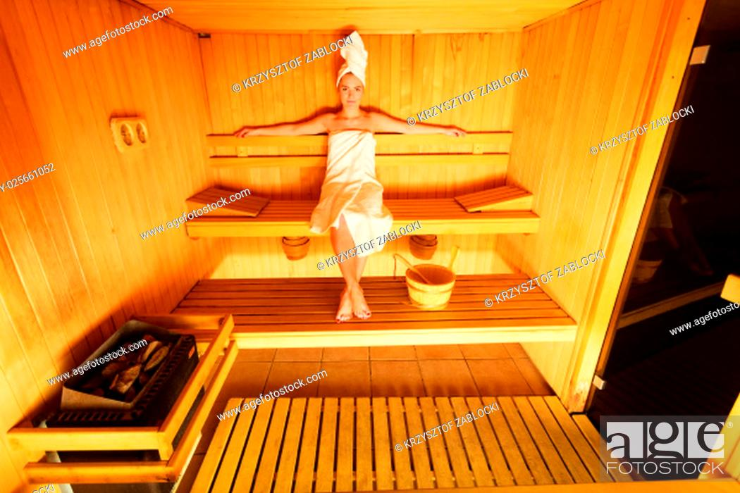 Stock Photo: spa beauty well being and relax concept. woman in full length white towel sitting relaxed in wooden sauna.