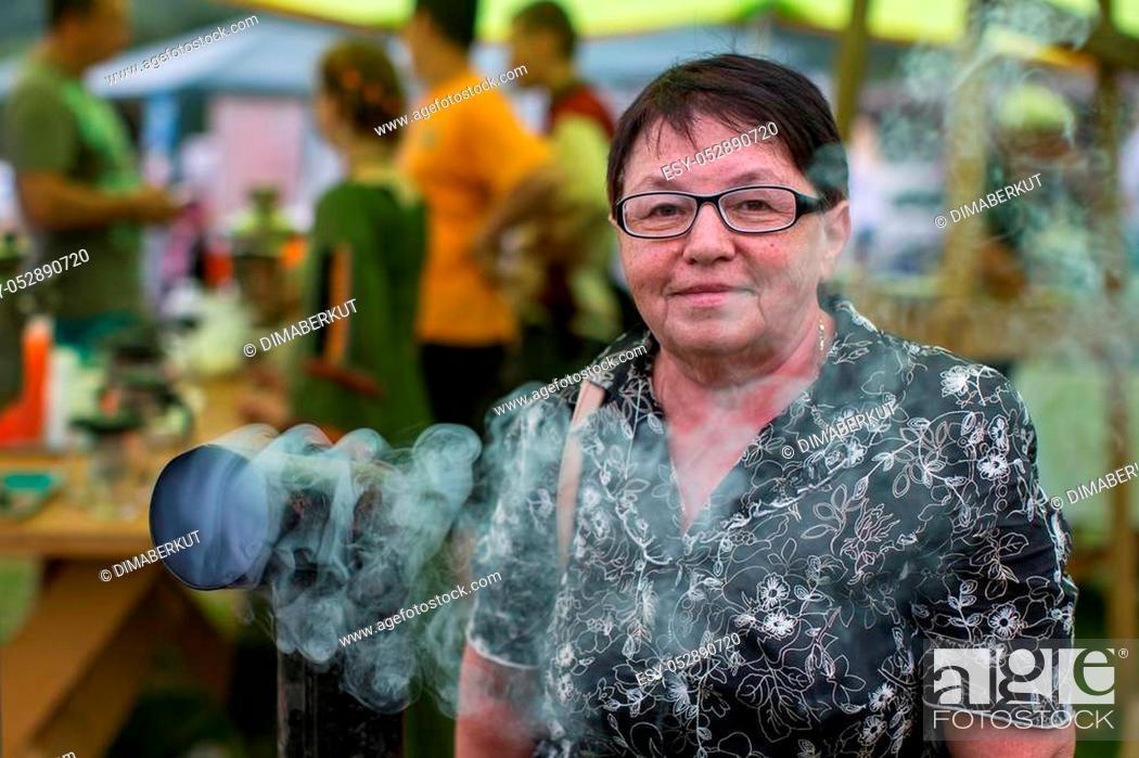 Stock Photo: Portrait of a woman at the folk fair near a Smoking samovar.
