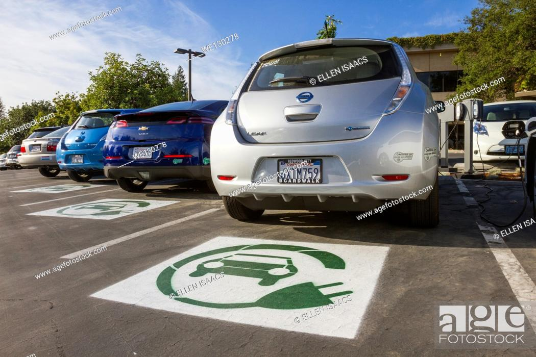 Stock Photo: EV symbol painted on parking spaces for to plug-in electric cars in a company parking lot.