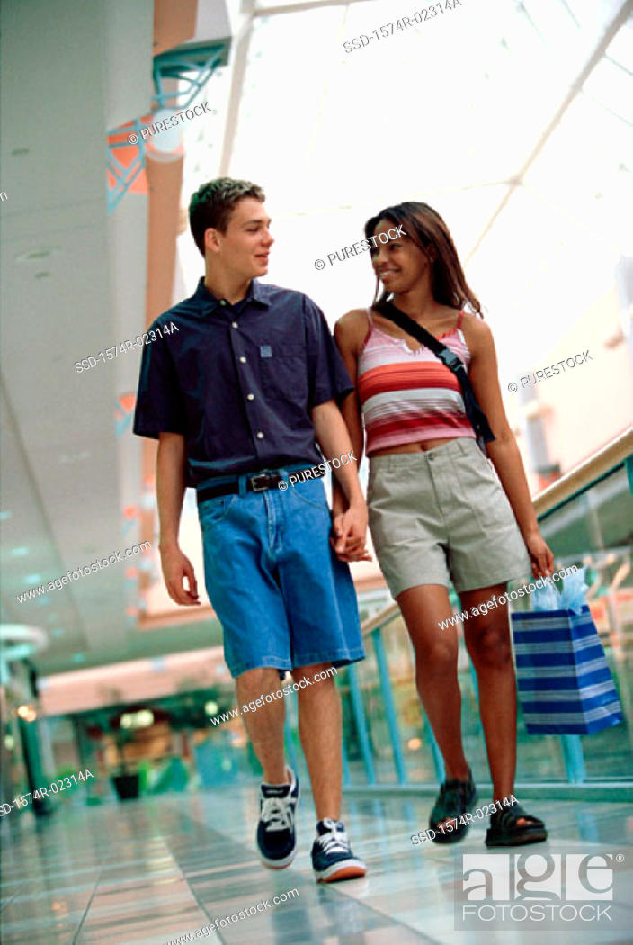Stock Photo: Young couple walking with a shopping bag in a shopping mall.