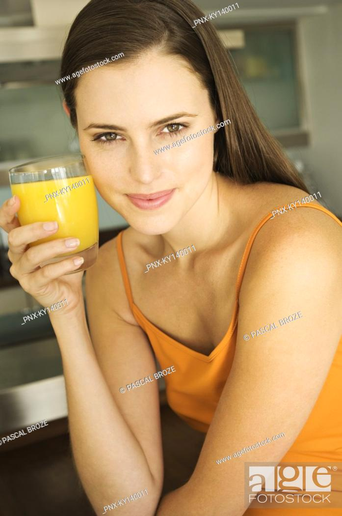 Stock Photo: Young woman holding glass of orange juice.