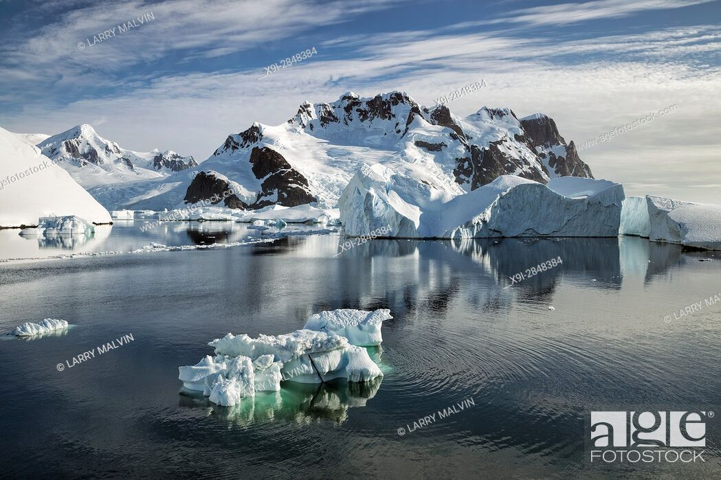 Imagen: Iceberg in the waters of the Lemaire Channel with mountains and glaciers along the Antarctic Peninsula.