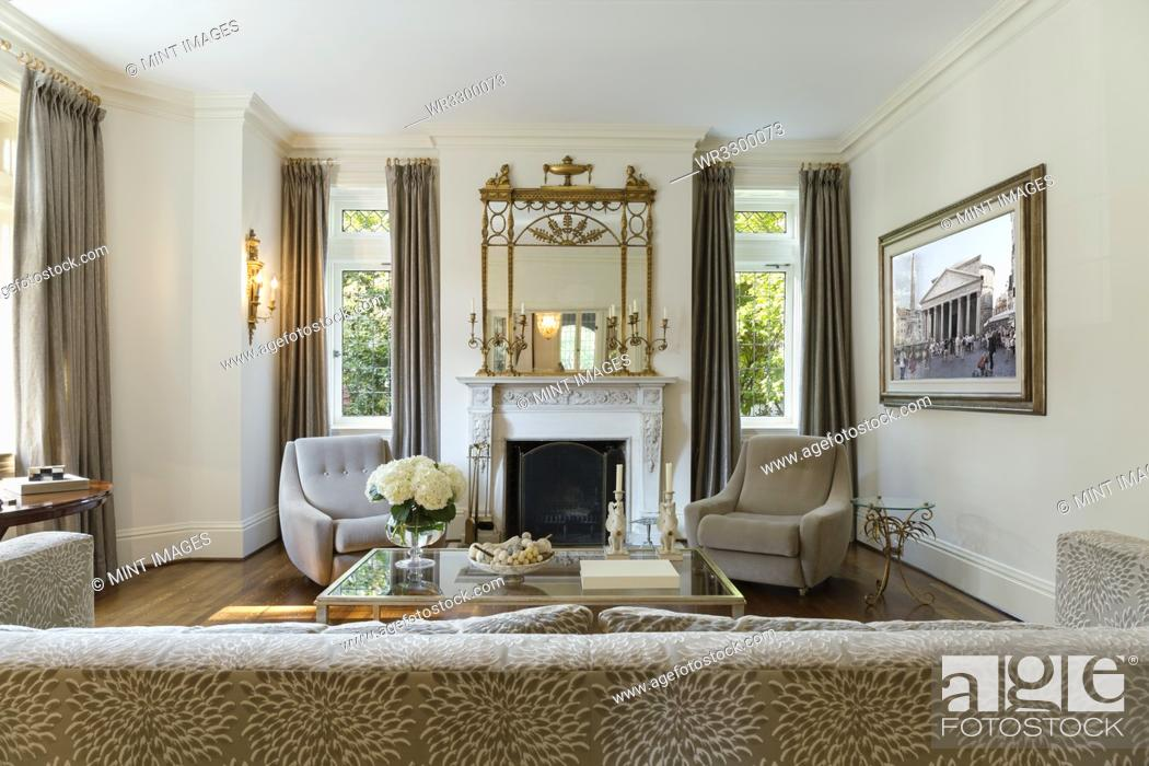 Photo de stock: Sofa and armchairs in ornate living room.