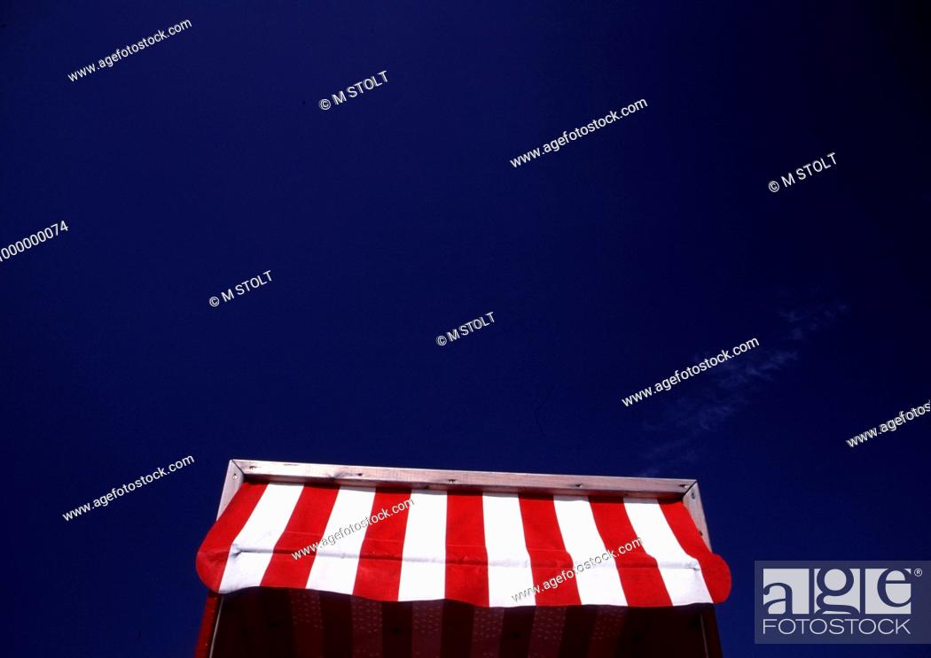 Stock Photo - Red and white striped awning of a beach chair
