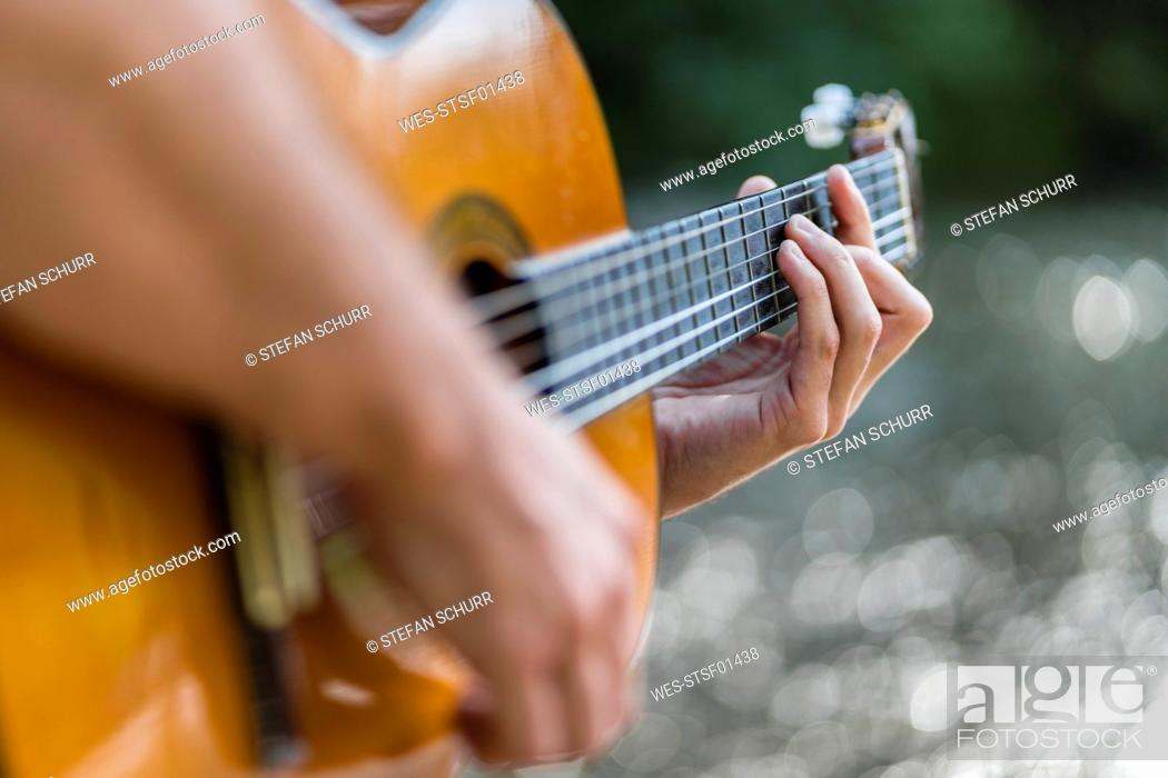Stock Photo: Man playing guitar in nature, close-up.