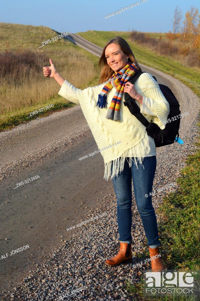 Imagen: Young hitch-hiking woman on a countryroad in Scania, Sweden.