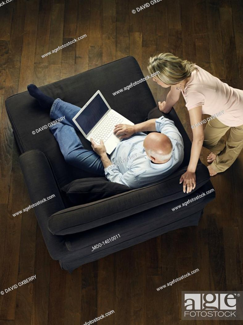 Stock Photo: Middle-aged man sitting on sofa using laptop woman leaning and watching view from above.