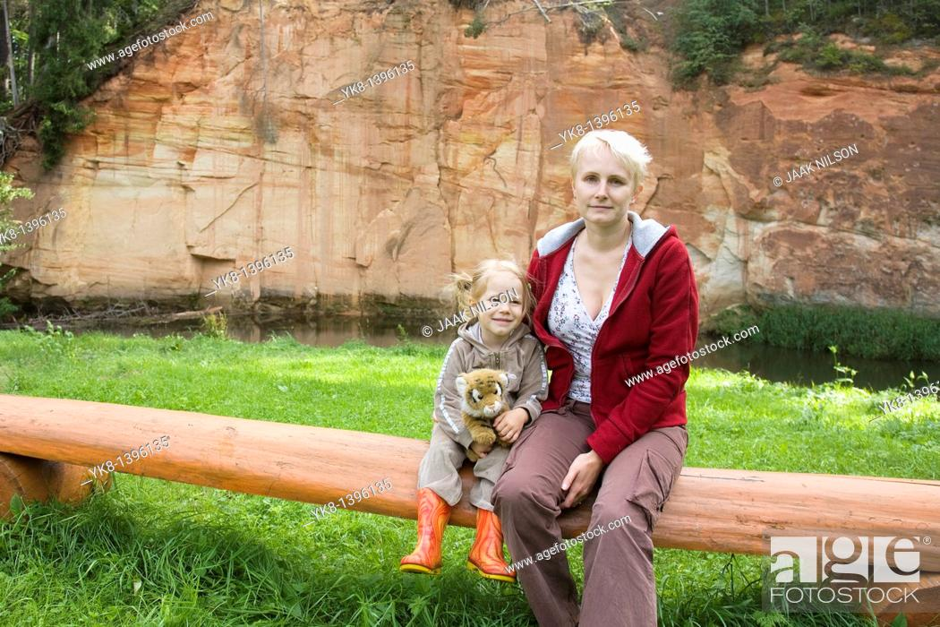 Stock Photo: Happy Kid Girl Sitting with Mother on Wooden Tree Trunk Bench by Sandstone Outcrop.