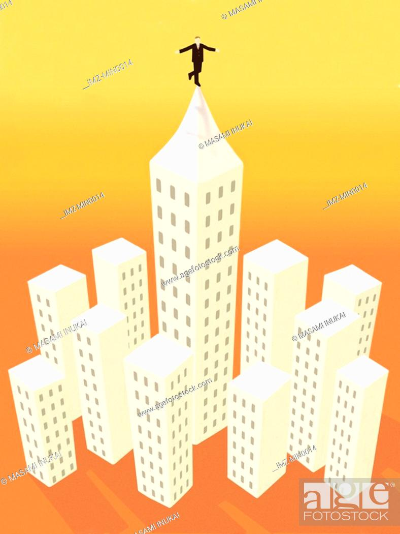 Stock Photo: A businessman balancing on one foot on top of the tallest building in a city.