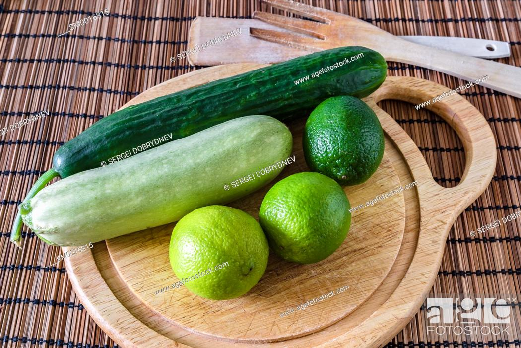 Stock Photo: Cucumber, zucchini, limes and cutting board lie on the kitchen table.