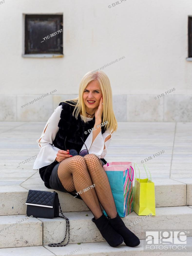 Stock Photo: Attractive shopper blonde woman is sitting on steps tired.