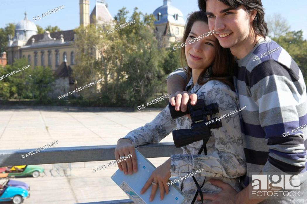 Stock Photo: Couple holding binoculars and a map outdoors smiling.