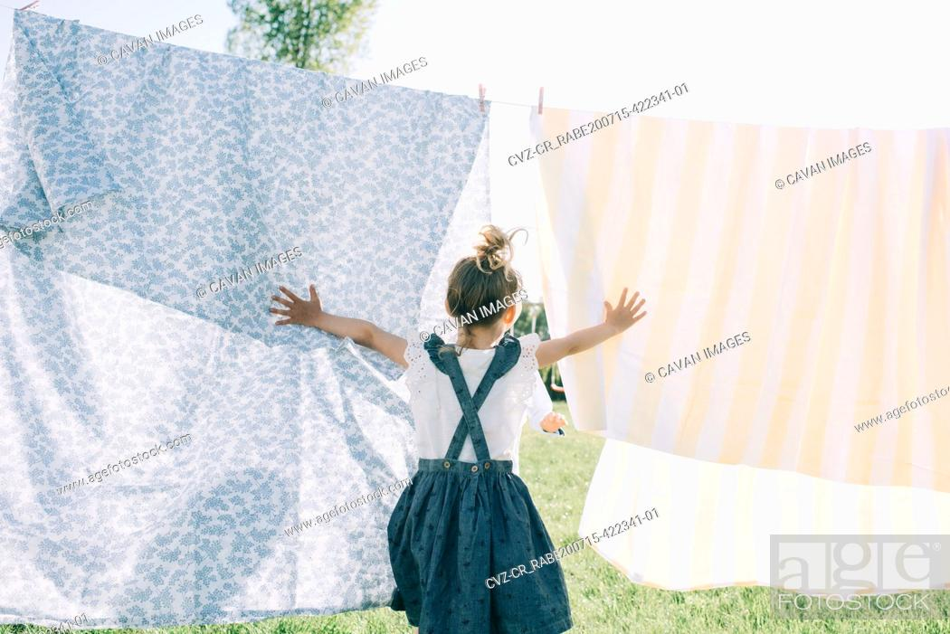 Stock Photo: young girl running through the washing on the line in the sun.