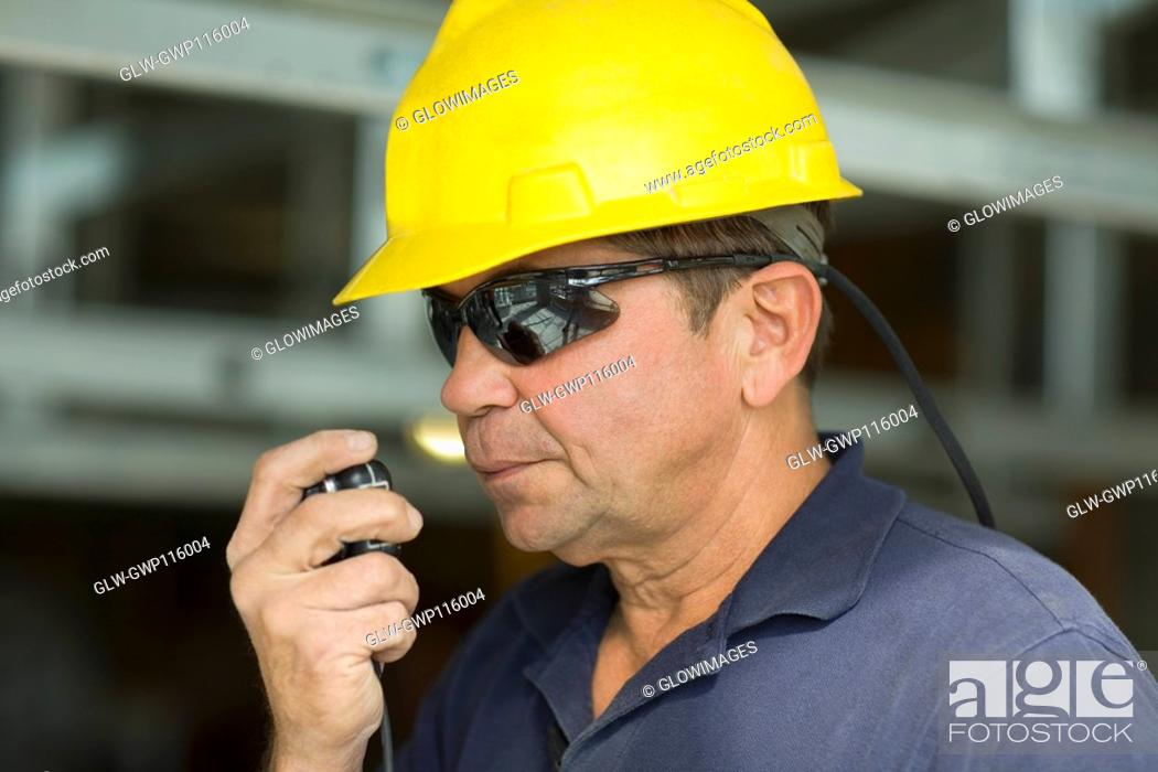 Stock Photo: Close-up of a male construction worker talking on a CB radio.