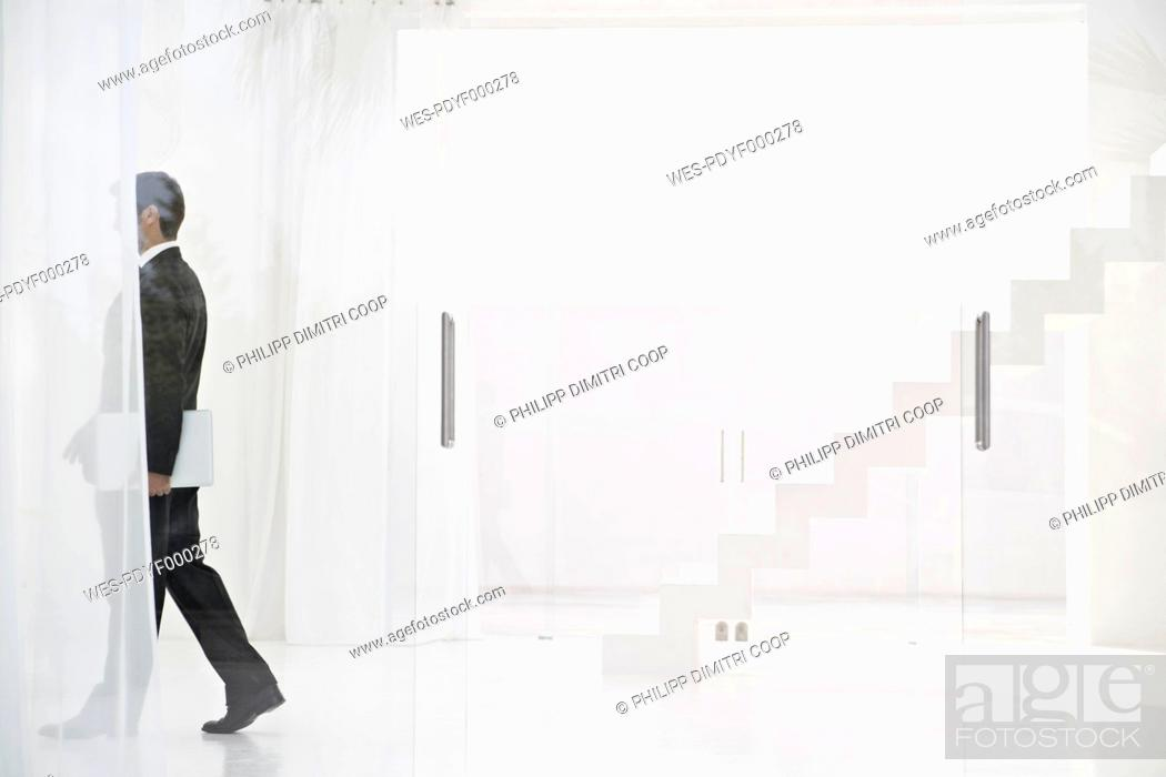 Stock Photo: Spain, Businessman walking with laptop.
