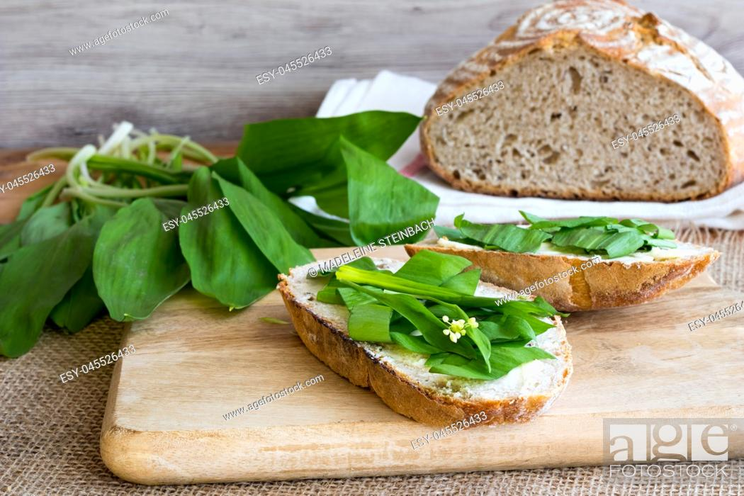 Stock Photo: Sourdough bread with butter and wild garlic leaves.