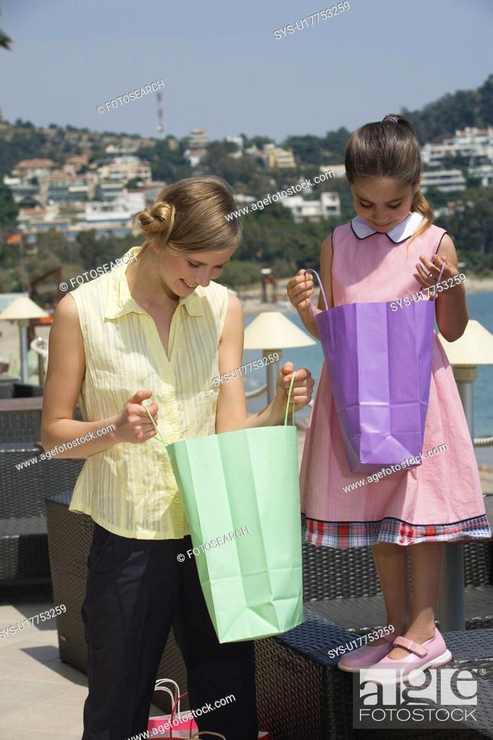 Stock Photo: Mother and daughter looking in shopping bags.