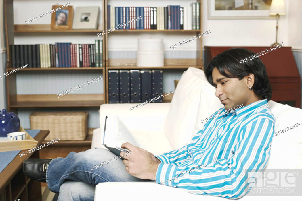 Stock Photo: Side profile of a young man reading a book.