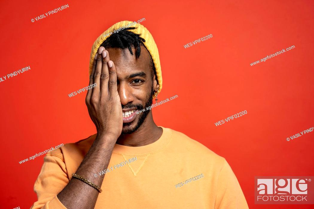 Stock Photo: Portrait of stylish young man covering one eye in front of orange wall.