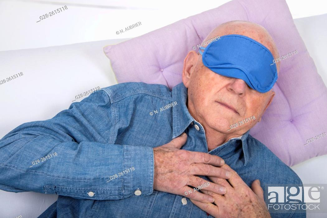 Stock Photo: Senior man quietly having an afternoon nap at home on a sofa.