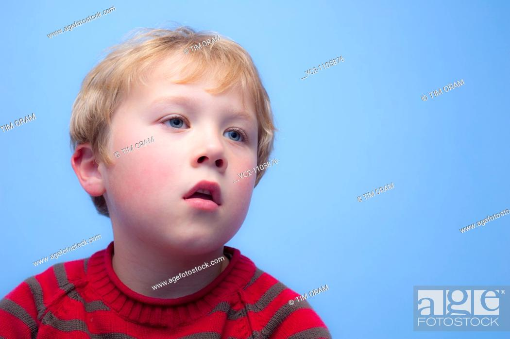 Stock Photo: 6 year old boy watching TV indoors in the Uk.