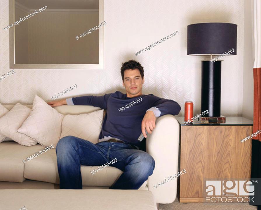 Stock Photo: Man watching television on sofa.