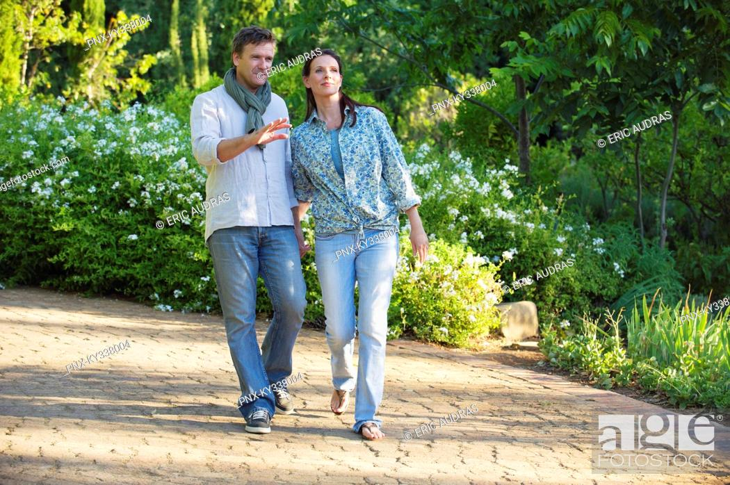 Stock Photo: Happy mature couple walking in a garden.