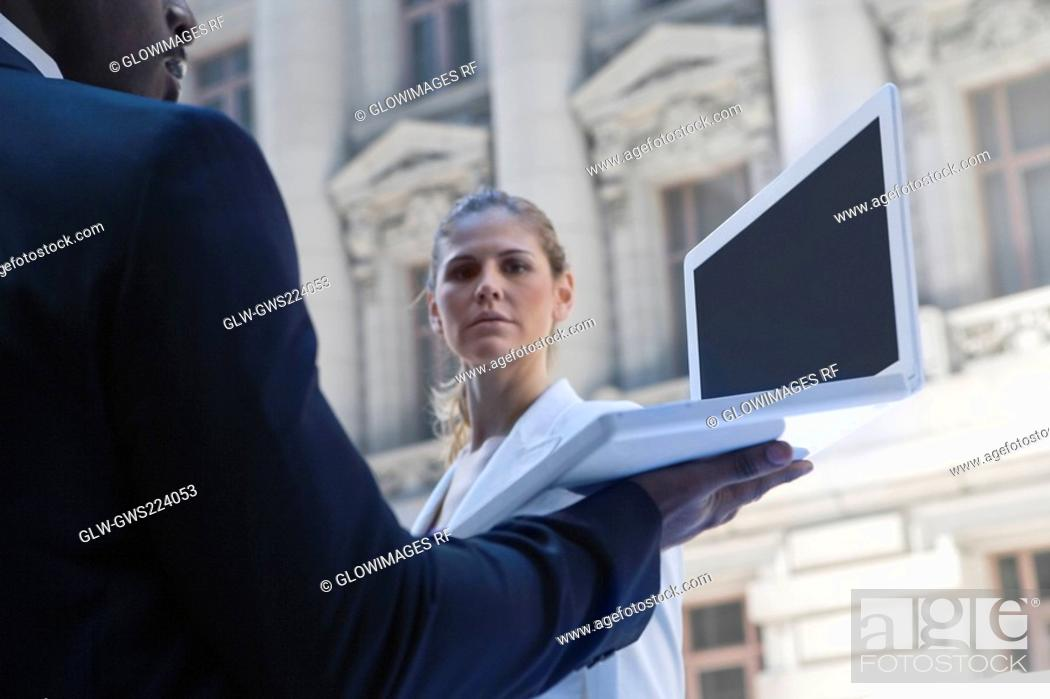 Stock Photo: Side profile of a businessman using a laptop with a businesswoman standing in front of him.