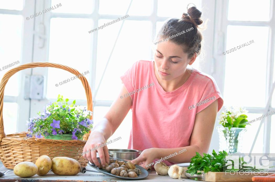 Stock Photo: Young woman preparing snails at kitchen counter, Vogogna, Verbania, Piemonte, Italy.