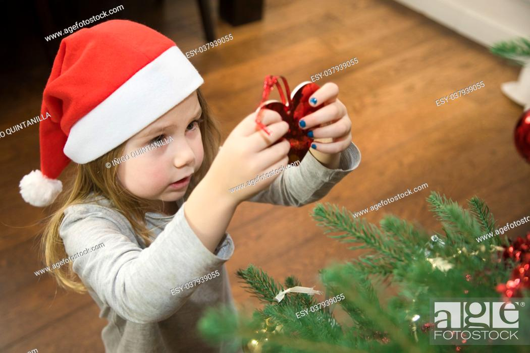 Stock Photo: four years blonde cute girl with red Santa Claus hat, placing red heart and decorating Christmas tree at home.