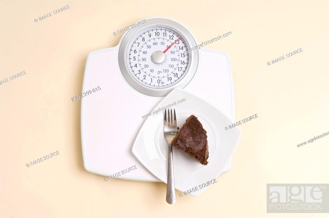 Stock Photo: Chocolate cake on weight scales.