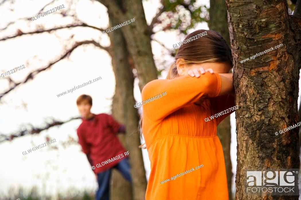 Stock Photo: Two children playing hide and seek in the forest.