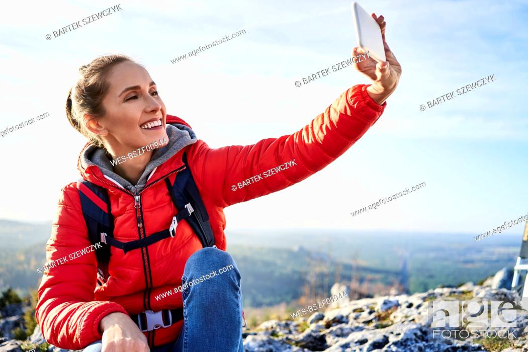 Stock Photo: Happy woman taking a selfie on a hiking trip in the mountains.