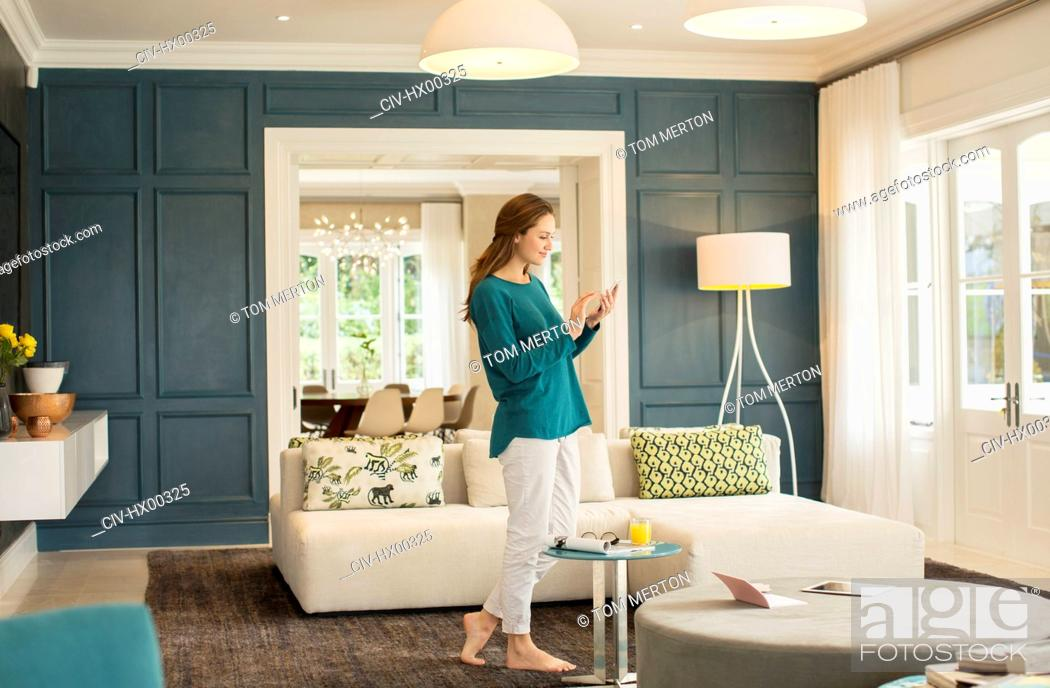 Stock Photo: Woman texting with cell phone in home showcase living room.