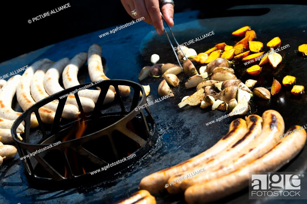 Stock Photo: 05 August 2018, Germany, Fulda: Shrimp sausages, pulled pork, yellow and red beetroot as well as garlic lie on a fire grill.
