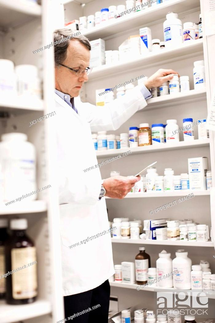 Stock Photo: Pharmacist looking at prescription and reaching for pill bottle.