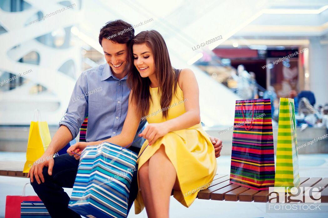Stock Photo: Happy couple peeking into shopping bag Debica, Poland.