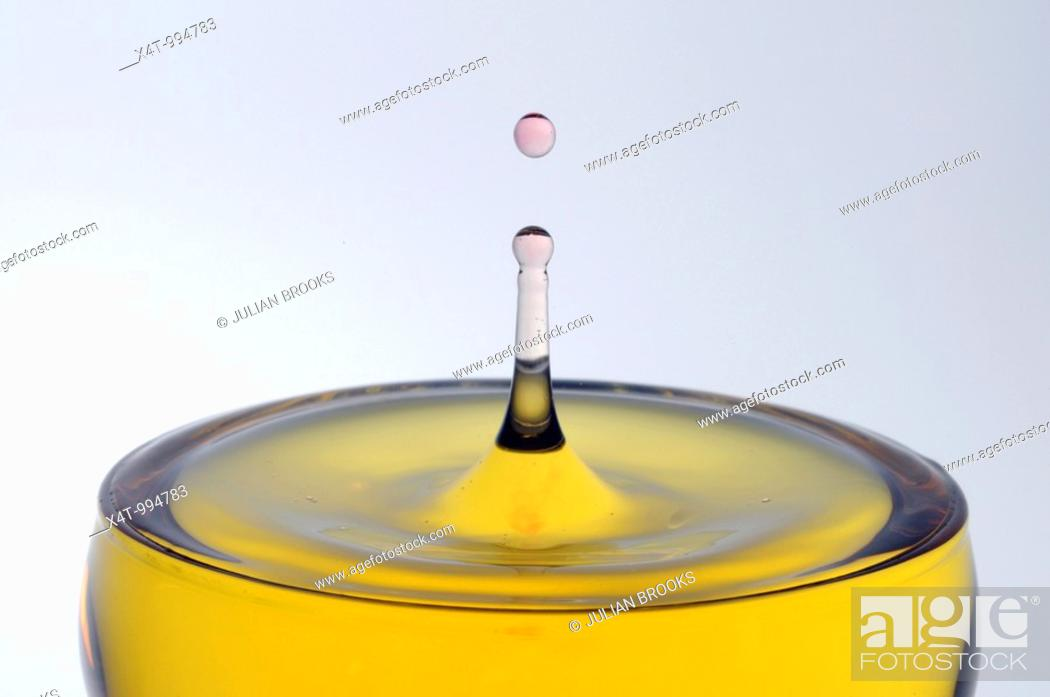 Stock Photo: A drop of pink water falling into a glass of yellow liquid forming a column with a drop on top.