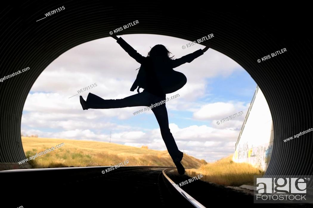 Stock Photo: Silhouette of a young woman jumping in a train tunnel.