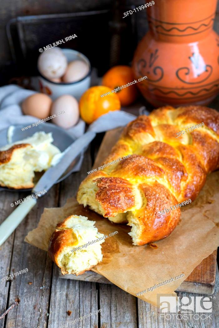 Stock Photo: A homemade Hefezopf (sweet bread plait from southern Germany) with orange zest with a chunk broken off for Easter.