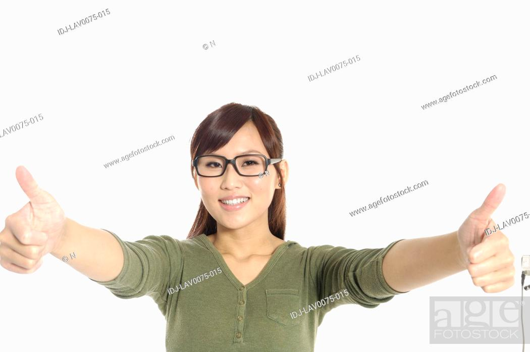 Stock Photo: Female university student showing thumbs up sign.