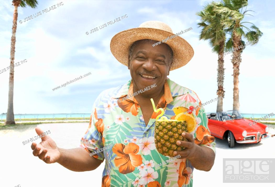 Stock Photo: African man holding pineapple drink on tropical beach.
