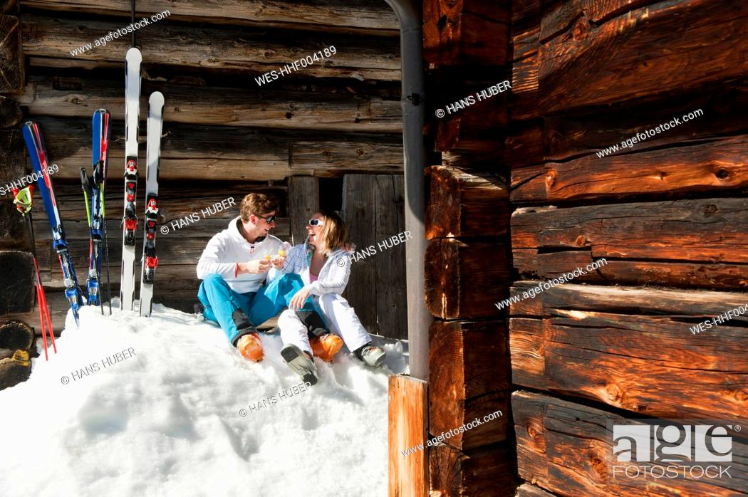 Stock Photo: Austria, Salzburg, Young couple sitting in front of alpine hut.
