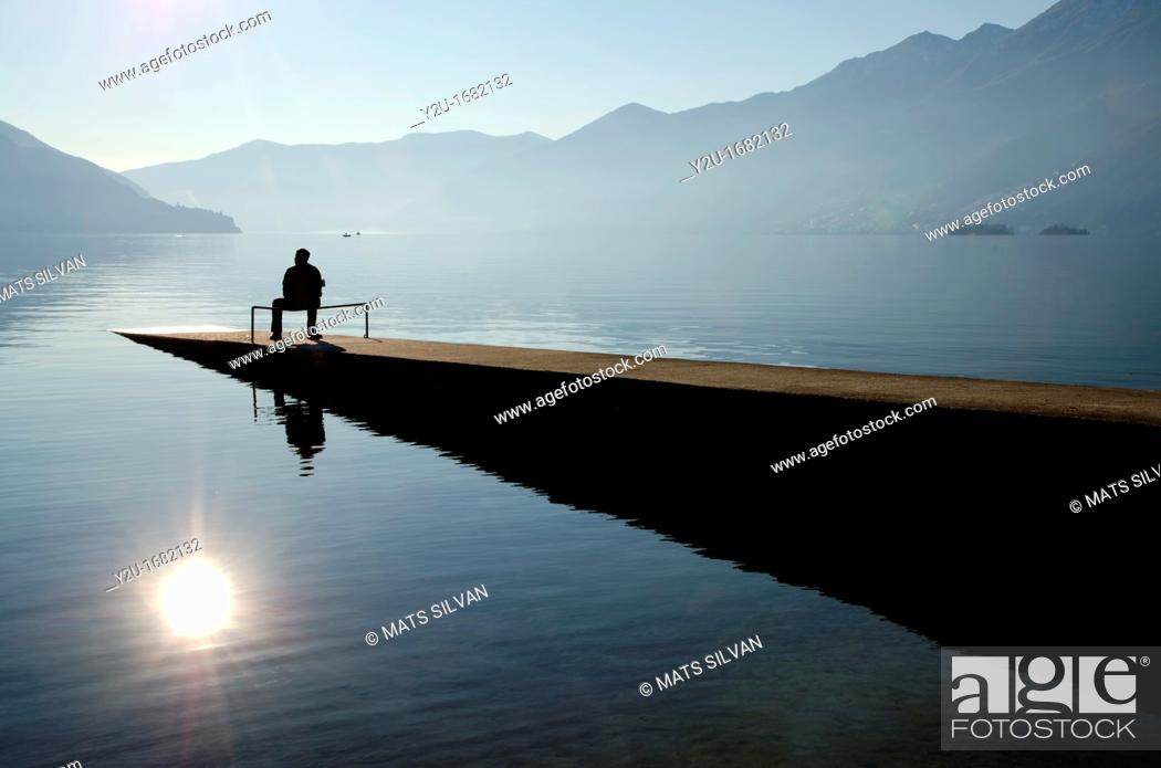 Stock Photo: Man sitting on the pier close to the lake with mountains and islands.