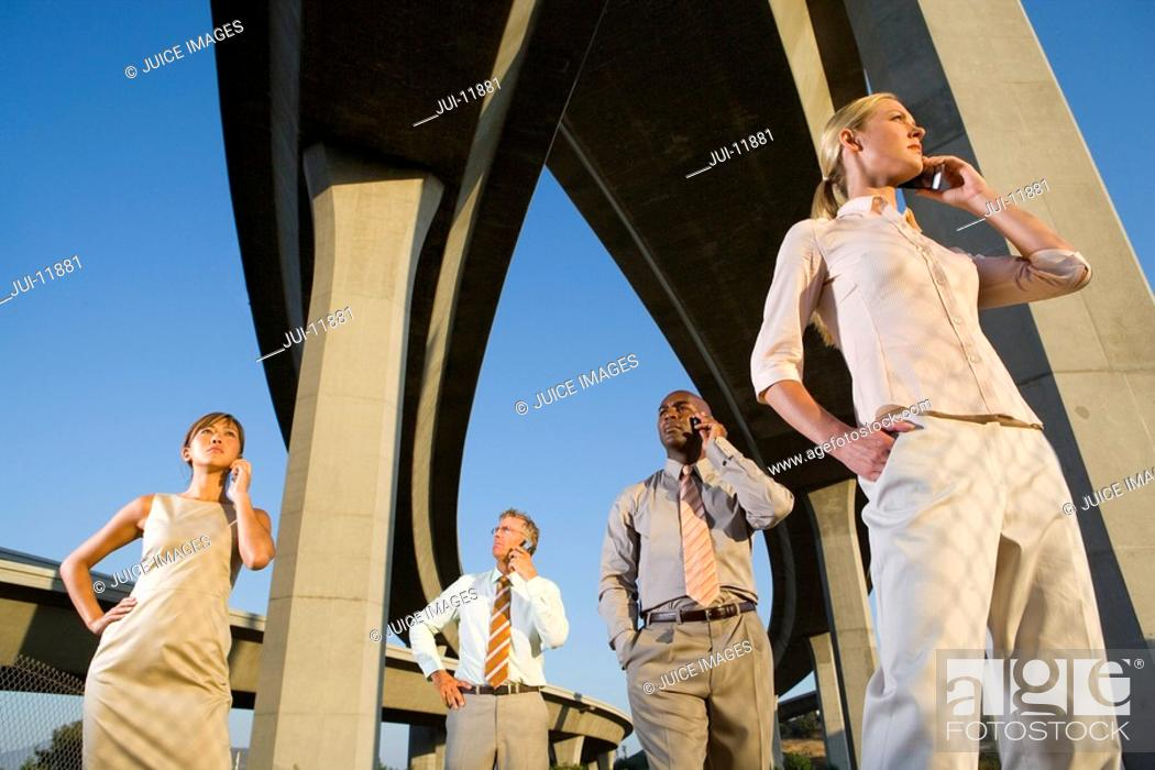Stock Photo: Small group of businesspeople using mobile phones beneath overpasses, low angle view.