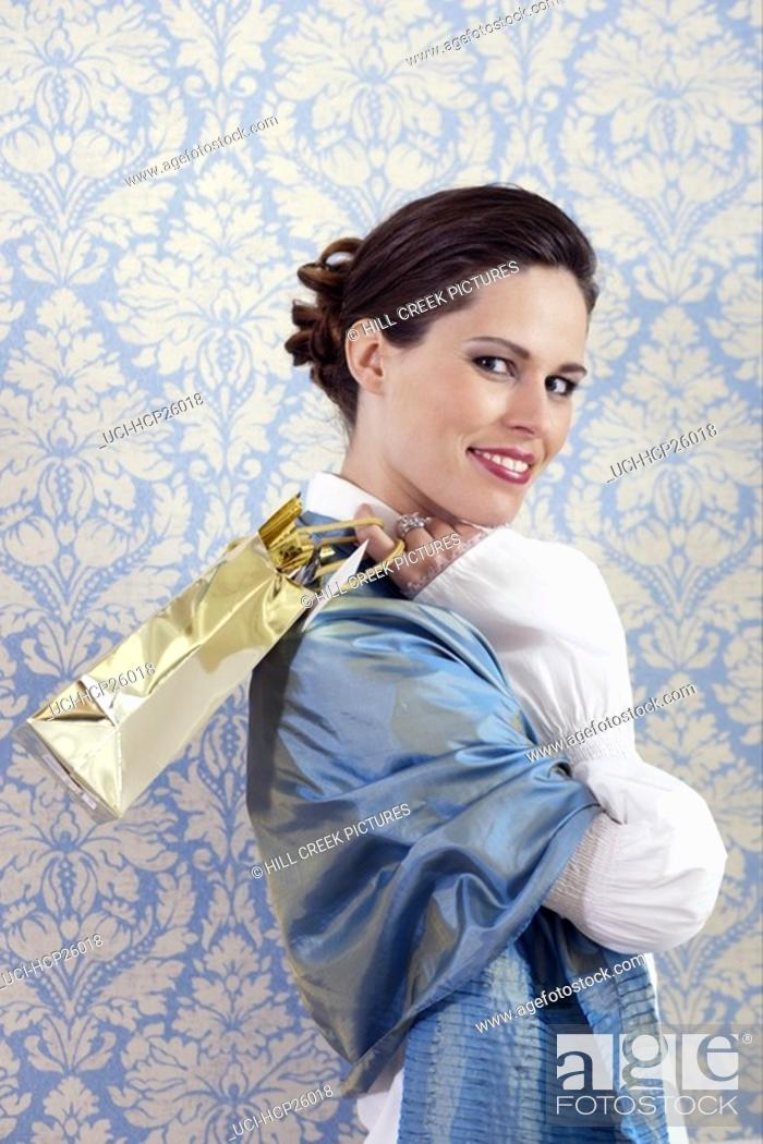 Stock Photo: Woman holding gift bag.