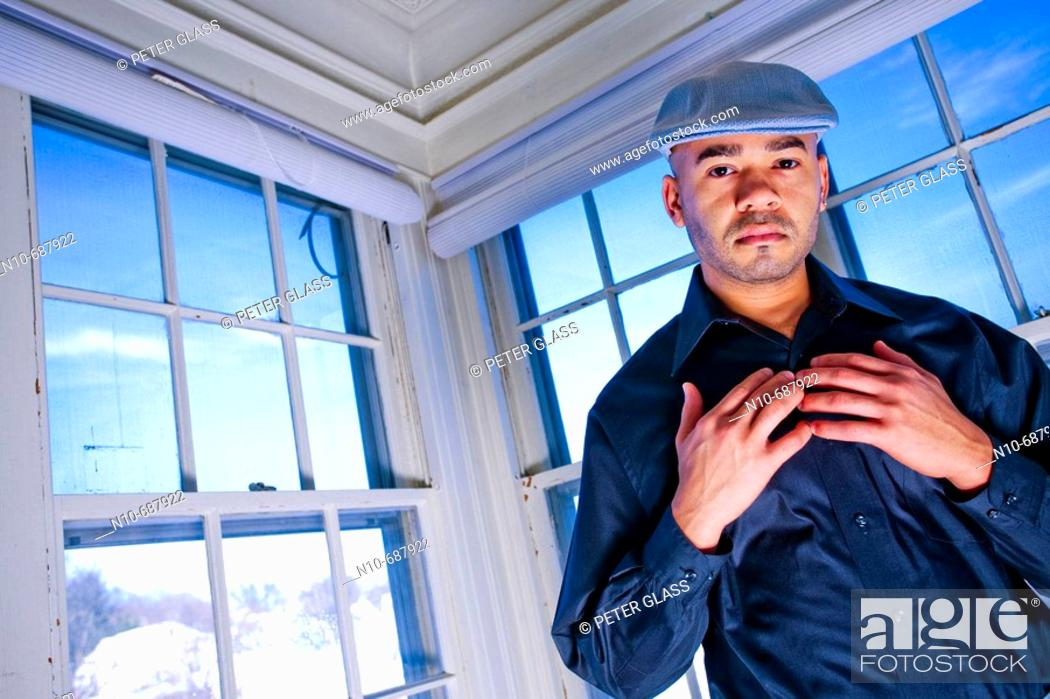 Stock Photo: Young Hispanic man, wearing a cap on his head, posing in front of several windows.