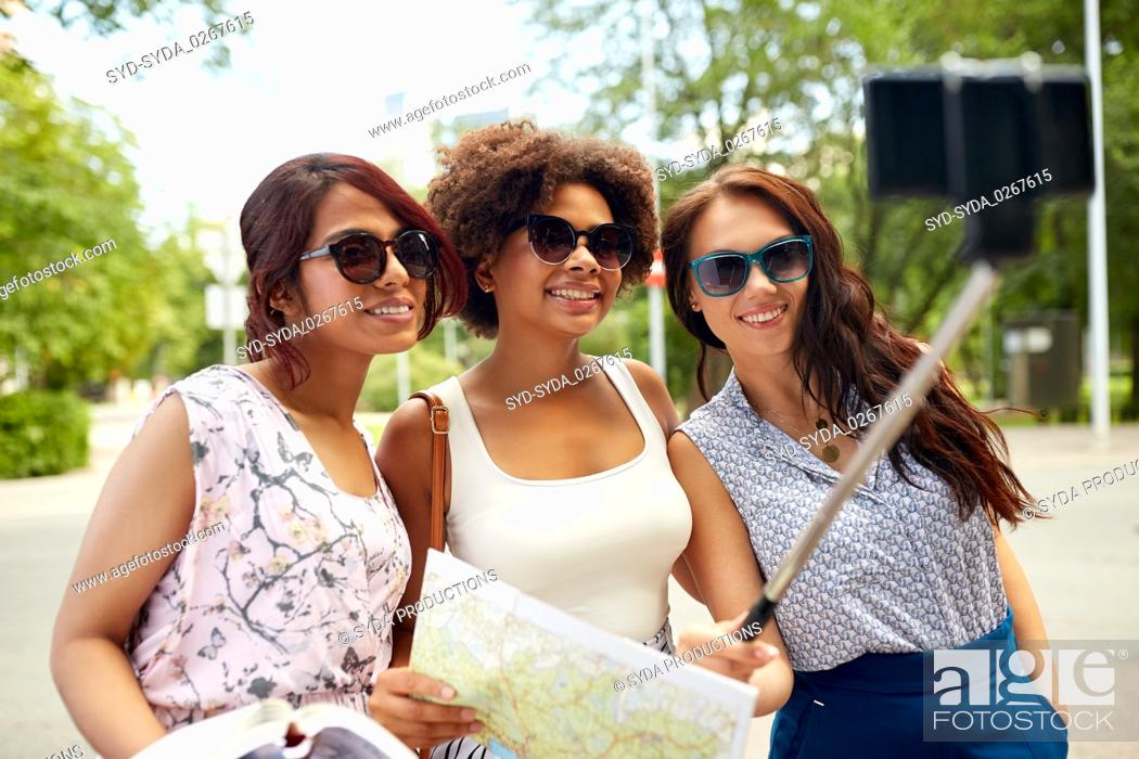 Photo de stock: women with city guide and map taking selfie.