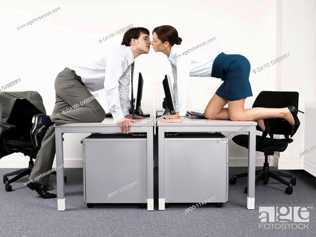 Stock Photo: Business couple kissing over desks in office.