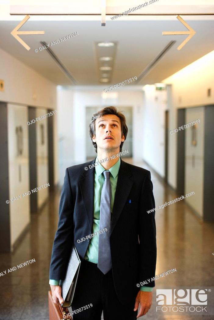 Stock Photo: Confused businessman in corridor looking up at arrows pointing opposite directions.